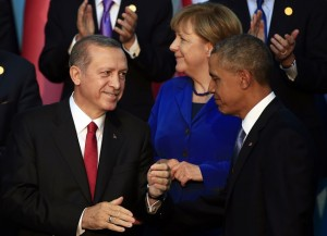 "President Barack Obama, right, is greeted by Turkish President Recep Tayyip Erdogan as German Chancellor Angela Merkel is seen in background, after posing for a family photo at the G-20 summit in Antalya, Turkey, Sunday, Nov. 15, 2015. U.S. President Barack Obama pledged Sunday to redouble U.S. efforts to eliminate the Islamic State group and end the Syrian civil war that has fueled its rise, denouncing the extremist group's horrifying terror spree in Paris as ""an attack on the civilized world."" (AP Photo/Lefteris Pitarakis)"